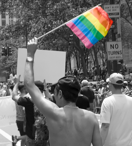 A man waves a rainbow flag, representing gay pride at the 2008 New York City Pride Parade/Creative Commons/By CarbonNYC