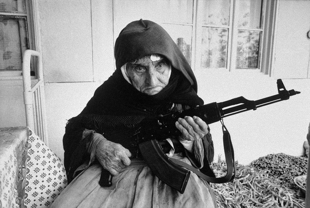 A 106-year-old Armenian woman sits in front of her home guarding it with a rifle, in the village of Degh, near the border of Azerbaijan. 1990.